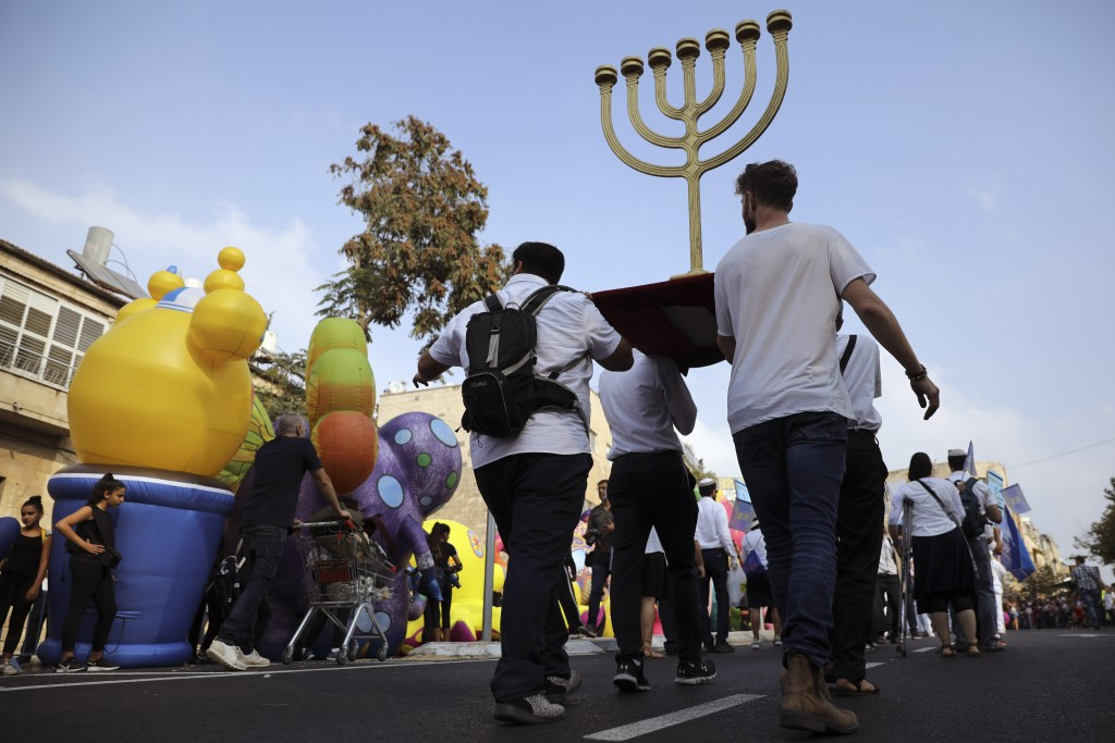 FILE - In this Oct. 17, 2019 file photo, people carry a Menorah as they participate in the annual support march for Israel, during the Jewish holiday ...