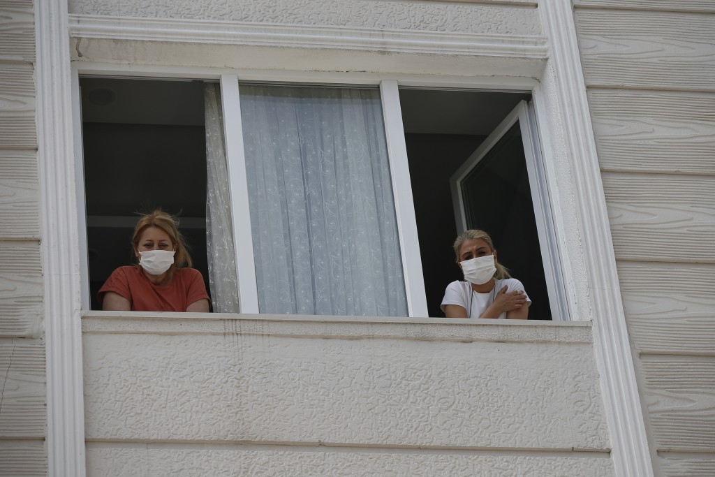 In this Friday, May 15, 2020 photo, Betul Sahbas, 47, right, who had been experiencing COVID-19 symptoms, looks from her flats's window in Istanbul as...