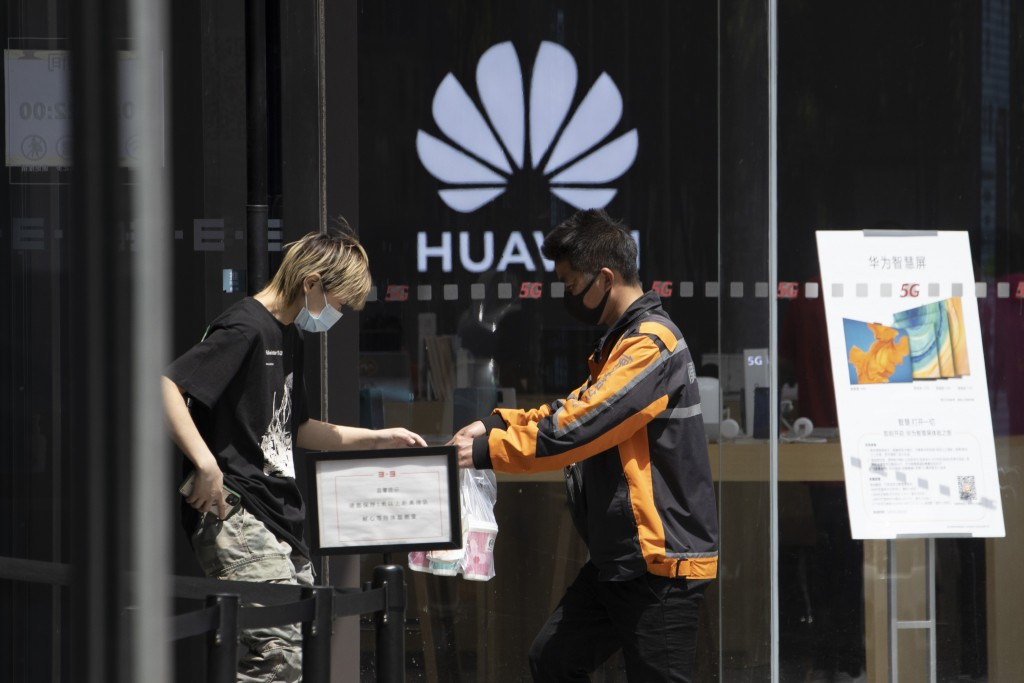 """A delivery man hands over drinks near a Huawei retail store in Beijing on Monday, May 18, 2020. China's commerce ministry says it will take """"all neces..."""