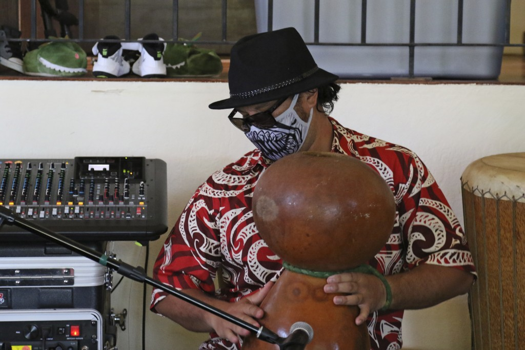 This May 5, 2020, photo shows Justin Chang playing a gourd during a livestream performance of his family's band, Kanilau, from the living room of his ...