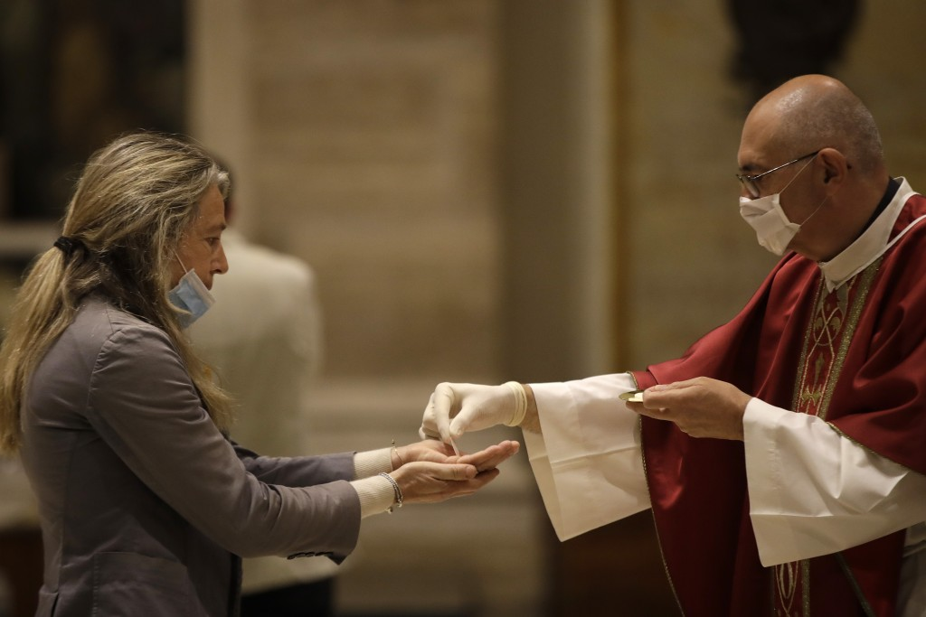 Father Jose Maria Galvan, wearing gloves to prevent the spread of COVID-19, places the host in the hands of a parishioner during the morning mass at S...