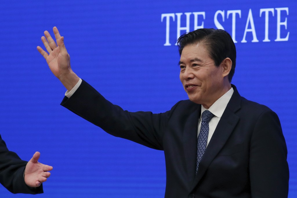 Chinese Commerce Minister Zhong Shan waves as he arrives for a press conference at the State Council Information Office in Beijing, Monday, May 18, 20...