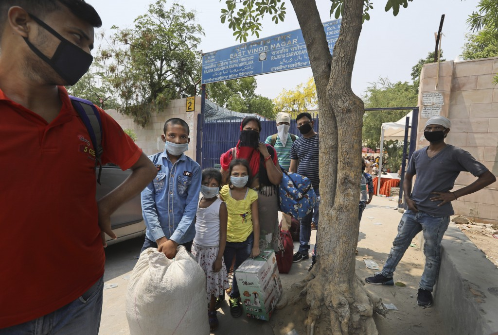 Migrant families from another state trying to return to their villages wait for transportation to Railway station in New Delhi, India, Monday, May 18,...
