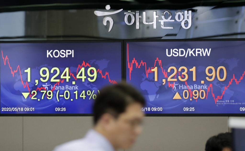 A currency trader walks near the screens showing the Korea Composite Stock Price Index (KOSPI), left, and the foreign exchange rate between U.S. dolla...