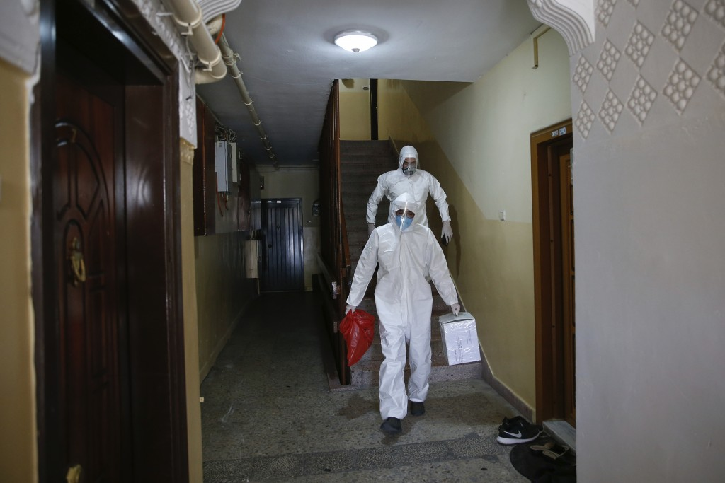 In this Friday, May 15, 2020 photo, contact tracers with Turkey's Health Ministry's coronavirus contact tracing team, clad in white protective gear, m...