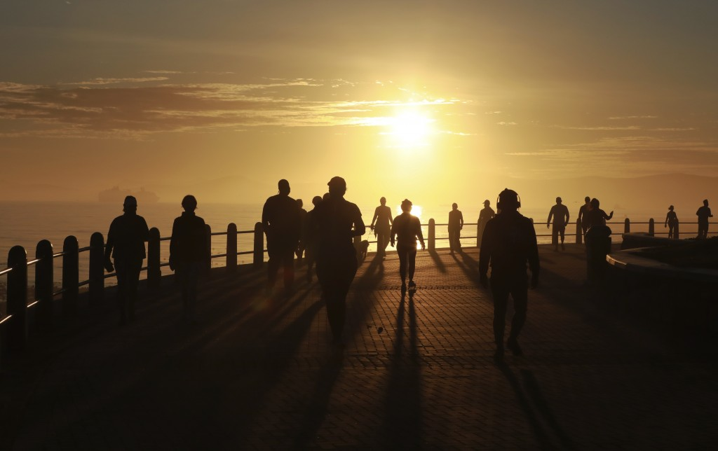 People exercise along the promenade at sunrise in Sea Point, Cape Town, South Africa, Monday. May 18, 2020 as the country marked day 53 of a governmen...