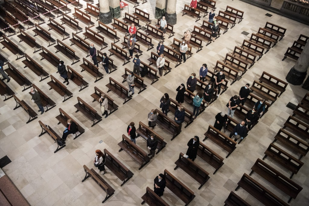 Faithful sitting in the benches, following the rules of social distancing, during a mass, the first day the presence of faithful was allowed during ma...