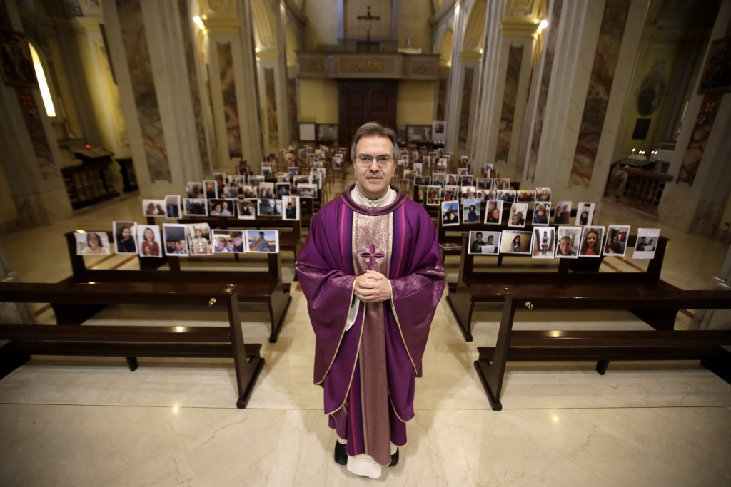 In this photo taken on March 15, 2020, Robbiano Church parson, Don Giuseppe Corbari, poses in front of selfies he was sent by parishioners as Masses f...