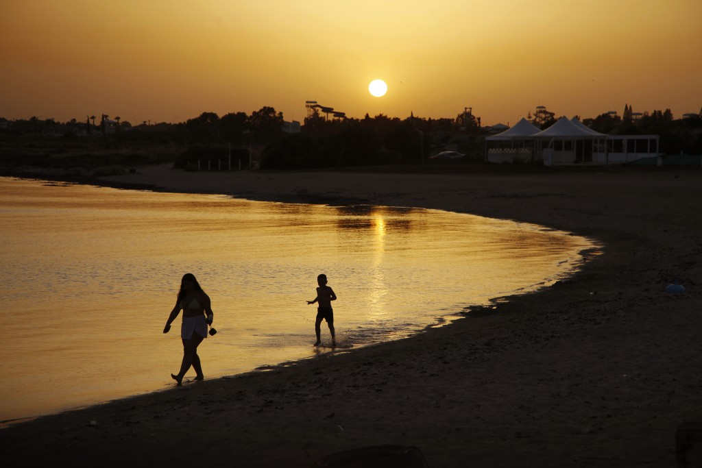 Beachgoers walks at the sea water during sunset at an empty stretch of Dome beach hotel at Makrinissos in Cyprus' seaside resort of Ayia Napa, a favor...