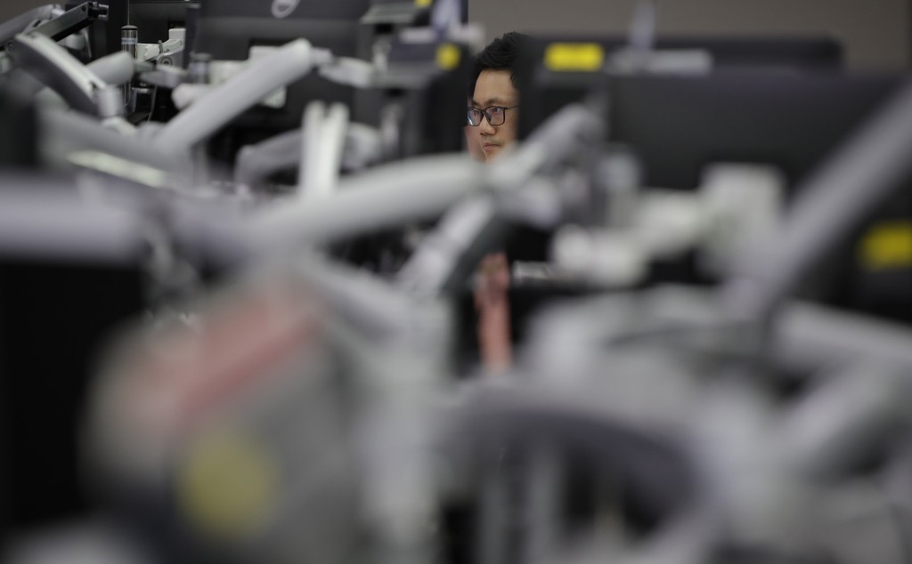 A currency trader watches computer monitors at the foreign exchange dealing room in Seoul, South Korea, Monday, May 18, 2020. Asian stock markets rose...