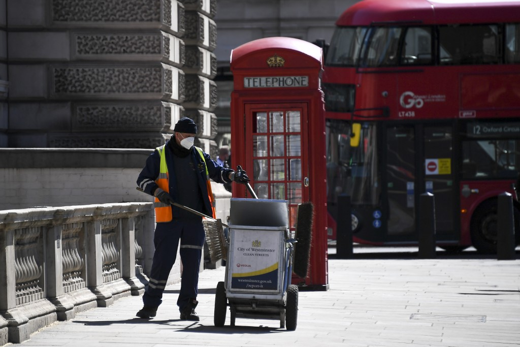 A council worker wearing a face mask to protect against coronavirus, collects refuse at Parliament Square, in London, Monday, May 18, 2020. Britain's ...