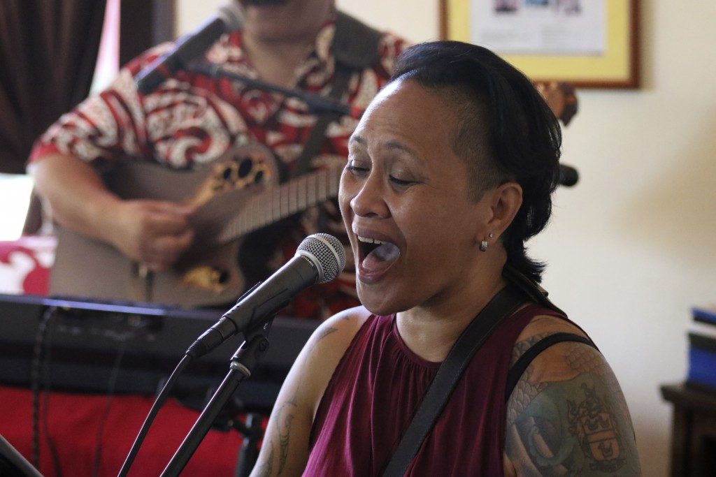 This May 5, 2020, photo shows NJ Chang singing during a livestream performance of her family's band, Kanilau, from the living room of her brother Rola...