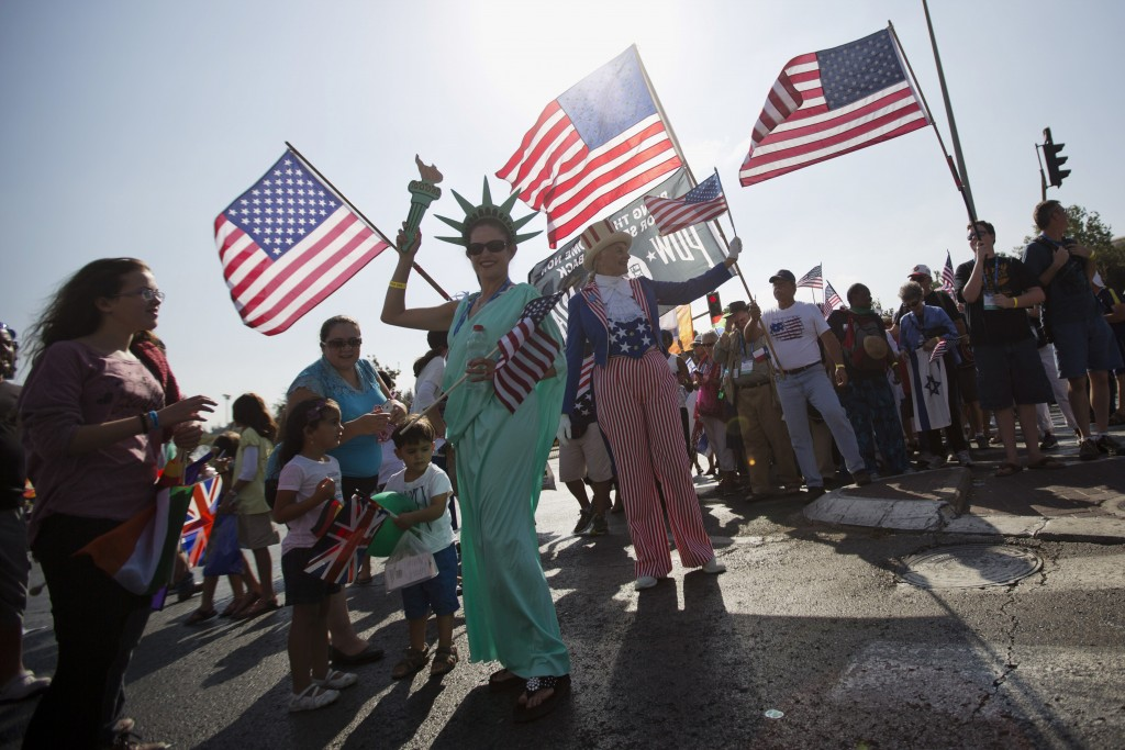 FILE - In this Oct. 1, 2015 file photo, evangelical Christians from various countries wave American flags in Jerusalem. An evangelical broadcaster who...