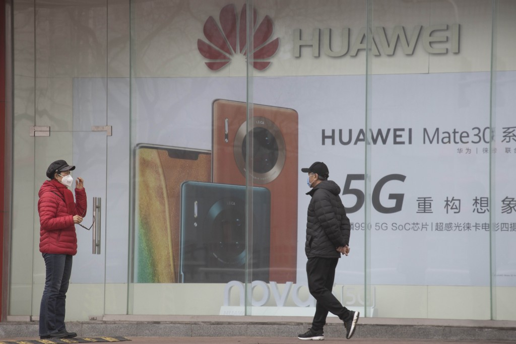 In this photo taken Sunday, March 8, 2020, residents wearing masks against the coronavirus walk past an Huawei advertisement in Beijing. China's comme...