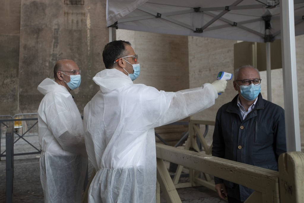 A visitor has his temperature checked in St. Peter's square at the Vatican in the day of the reopening of St. Peter's Basilica, Monday, May 18, 2020. ...