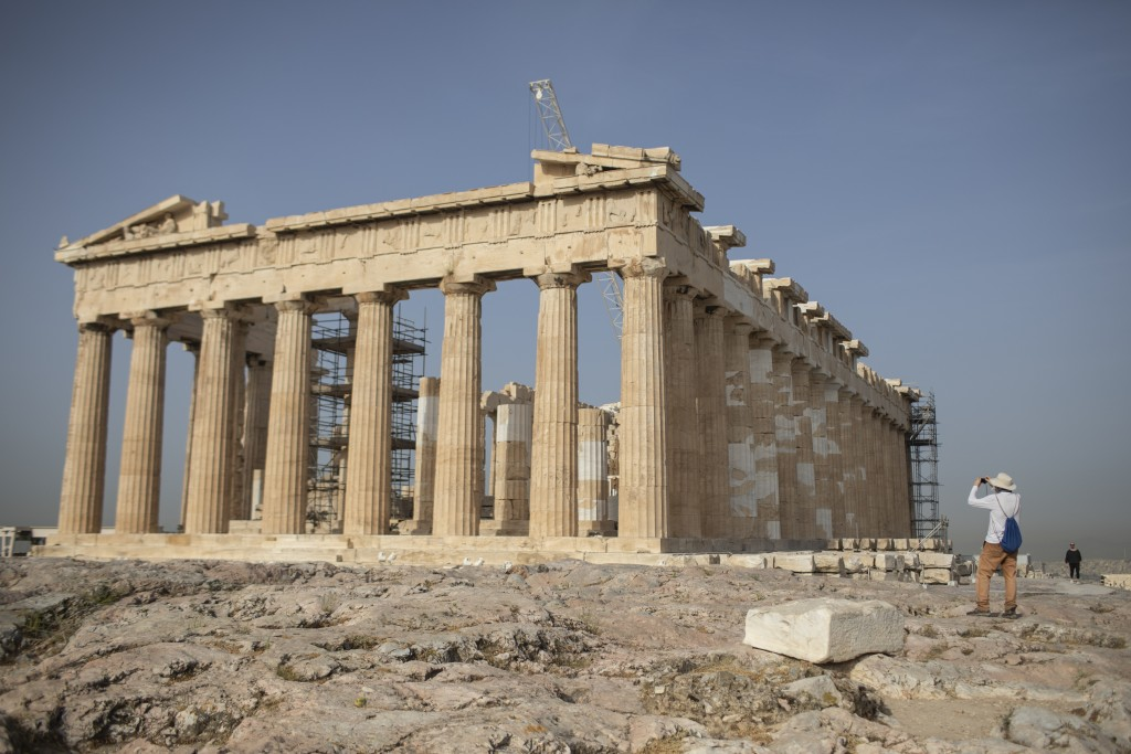 A man takes a picture next the ancient Parthenon temple at the Acropolis hill of Athens, on Monday, May 18, 2020. Greece reopened the Acropolis in Ath...
