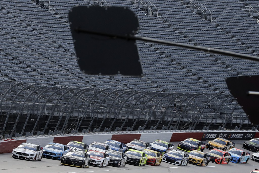 Cars approach the starting line in front of empty stands to start the NASCAR Cup Series auto race Sunday, May 17, 2020, in Darlington, S.C. (AP Photo/...
