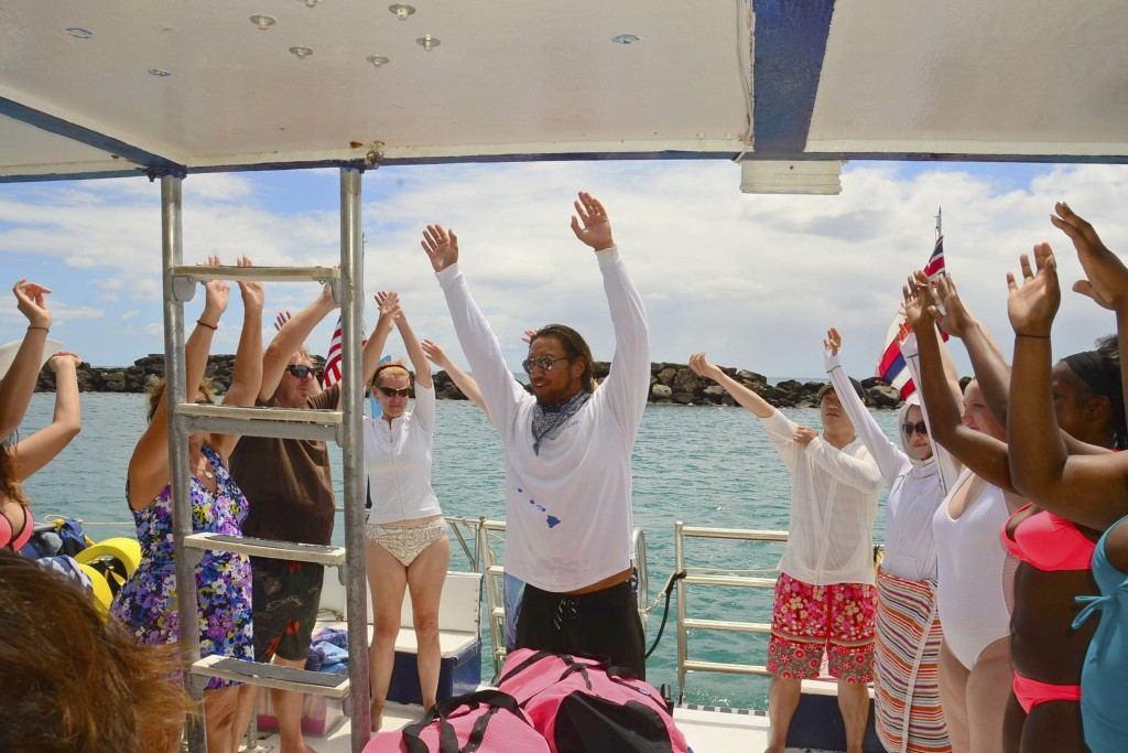 This undated photo provided by EO Waianae Tours shows Justin Chang teaching hula to passengers on board a tour boat in Waianae, Hawaii. The coronaviru...