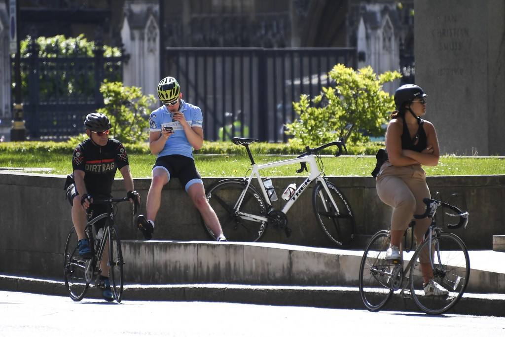 Cyclists wait at Parliament Square, in London, Monday, May 18, 2020. Large areas of London are to be closed to cars and vans to allow people to walk a...