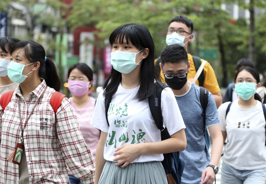 People wearing face masks to protect against the spread of the coronavirus travel around Taipei, Taiwan, Monday, May 18, 2020. (AP Photo/Chiang Ying-y...