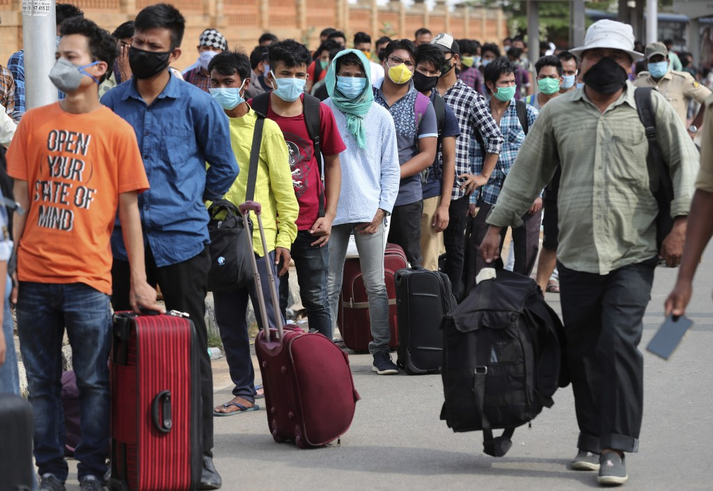 Stranded migrant workers line up to board buses before taking a special train to their destination during extended lockdown to curb the spread of new ...