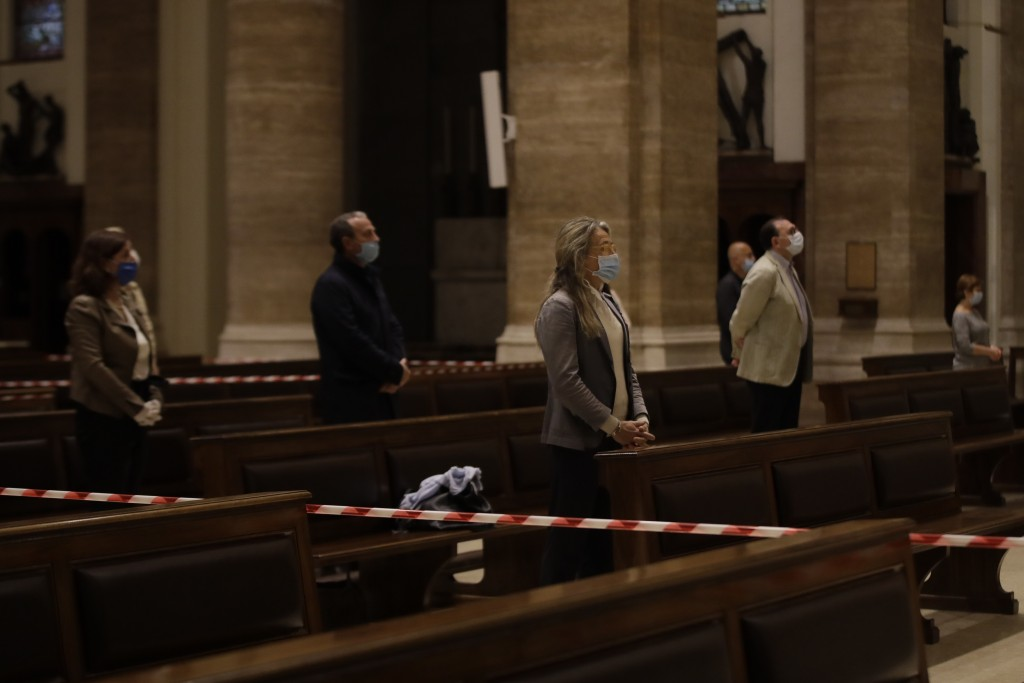 Faithful wearing gloves and face masks to prevent the spread of COVID-19, pray during the morning mass at St. Eugenio Church, in Rome, Monday, May 18,...