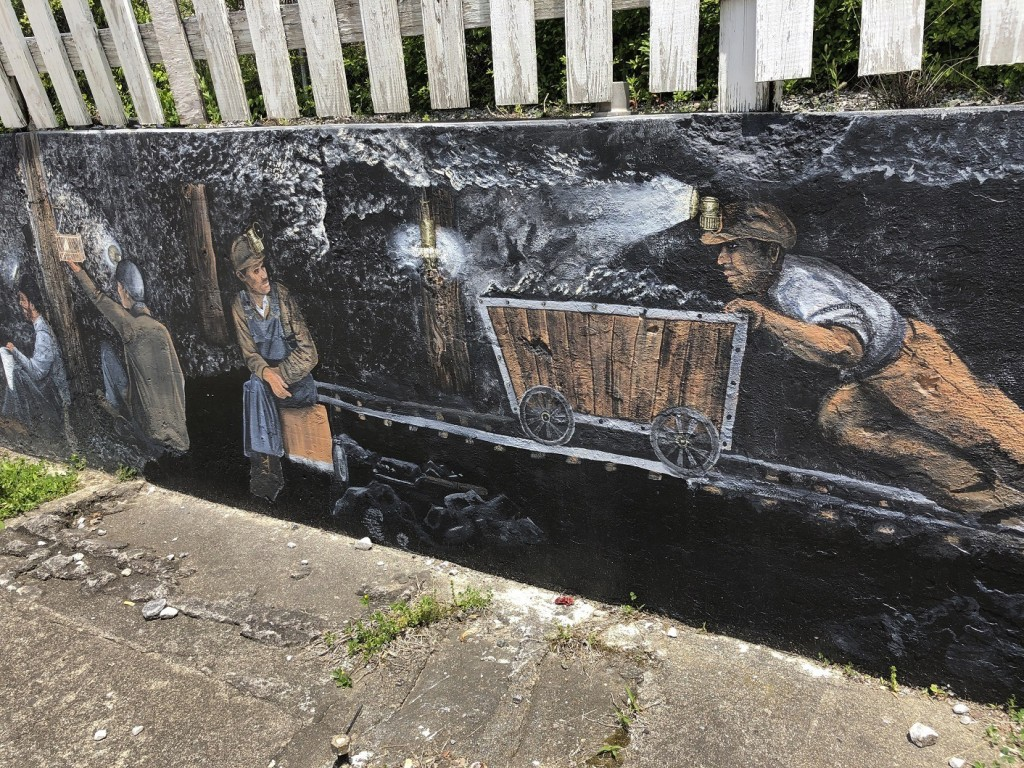 In this Tuesday, May 12, 2020, photo is a mural depicting miners working in coal mines in Matewan, W.Va. On May 19, 1920, a group of miners, who were ...
