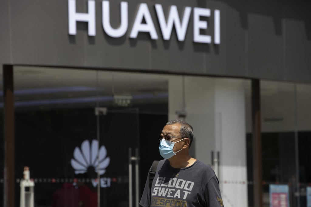 A man wearing a face mask to protect against the coronavirus walks past a Huawei retail store in Beijing on Monday, May 18, 2020. China's commerce min...