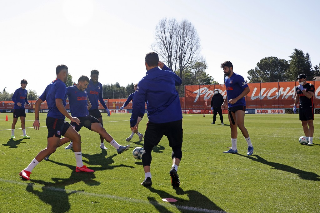 In this photo provided by Atletico Madrid, team players take part in the first group training session in Madrid, Spain, Monday May 18, 2020. All Spani...