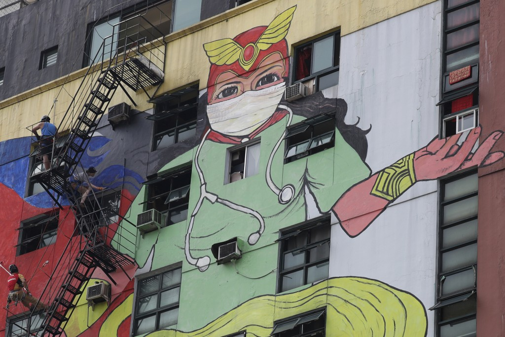 Artists paint mural of Darna, fictional Filipino comics superhero, wearing protective mask, scrub suit in Manila, Philippines.
