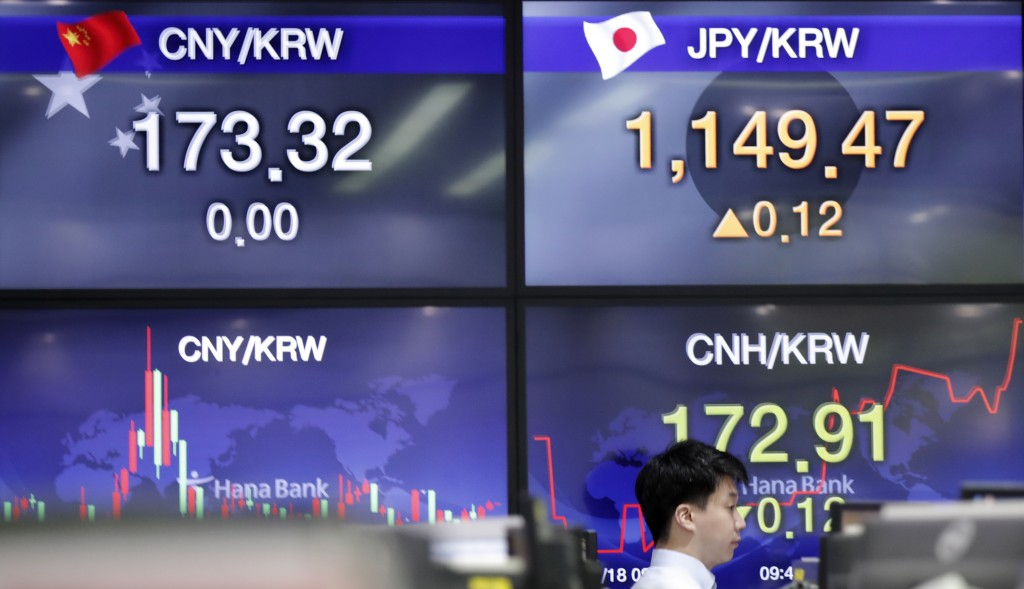 A currency trader walks by the screens showing the foreign exchange rates at the foreign exchange dealing room in Seoul, South Korea, Monday, May 18, ...