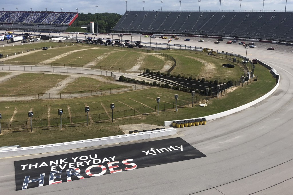 Cars go through a turn past a sign thanking people working during the coronavirus pandemic at Darlington Raceway Sunday, May 17, 2020, in Darlington, ...
