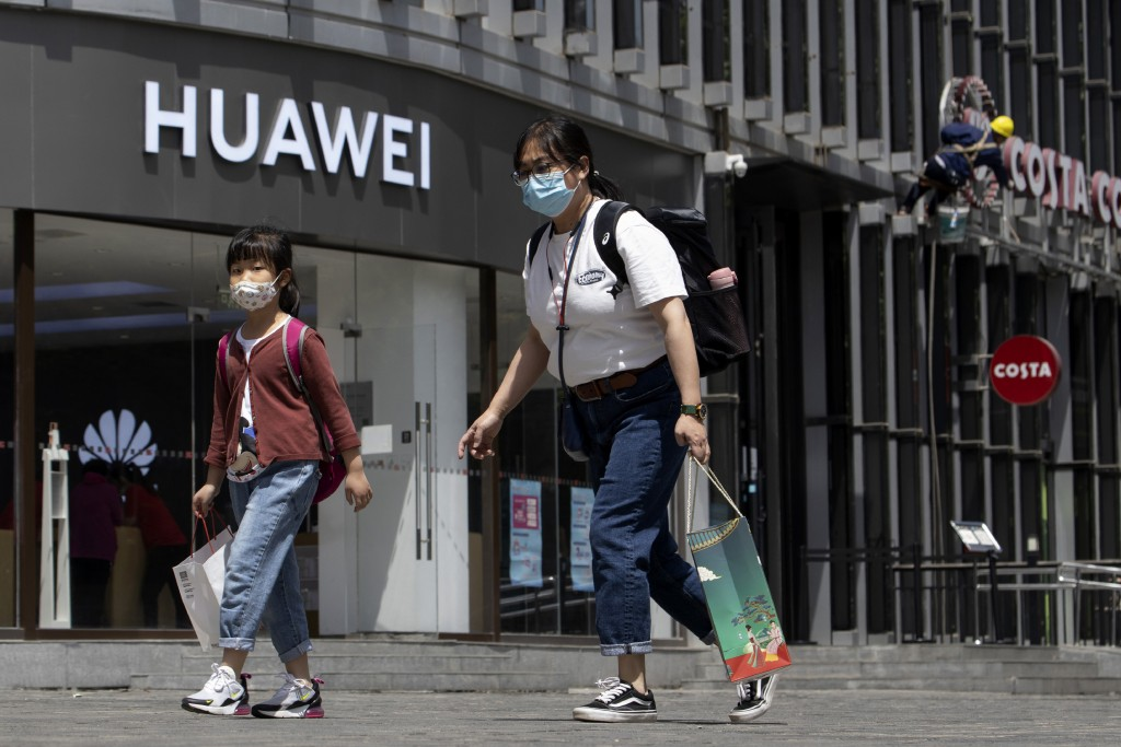 Residents wearing face masks to protect against the coronavirus walk past a Huawei retail store in Beijing on Monday, May 18, 2020. China's commerce m...