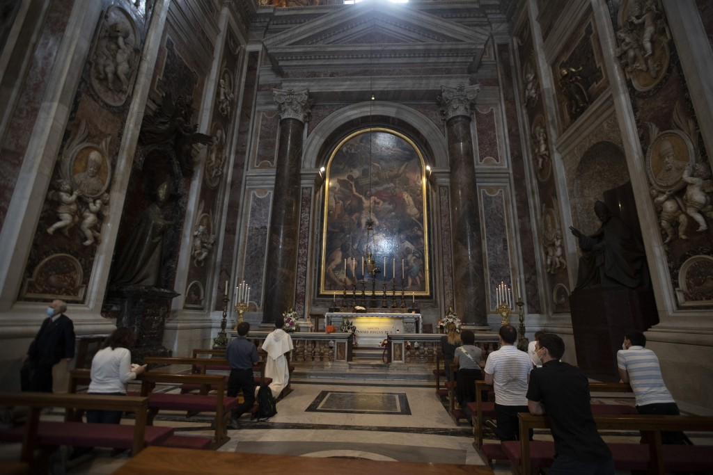 People wearing face masks to prevent the spread of COVID-19 pray in John Paul II chapel in St. Peter's Basilica at the Vatican in the day of its reope...