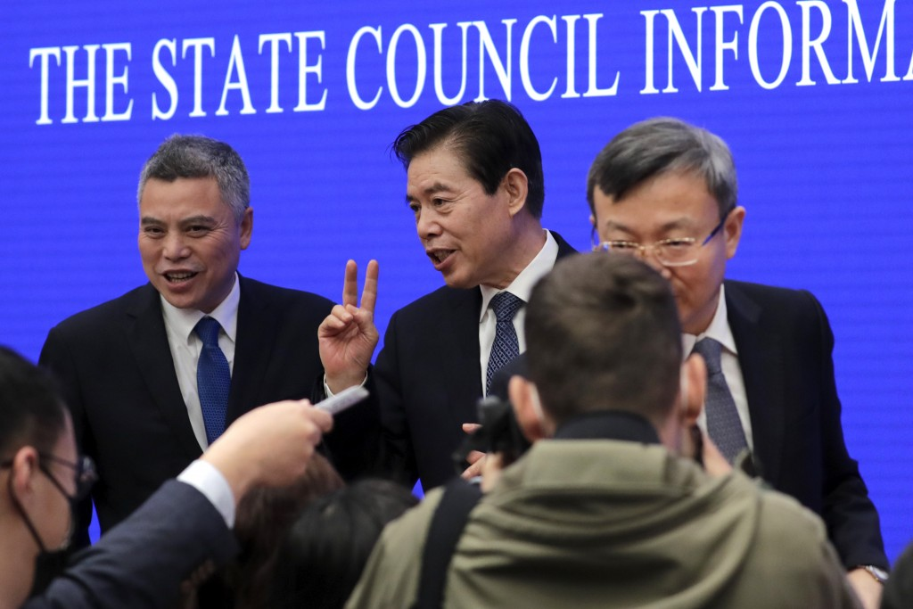 Chinese Commerce Minister Zhong Shan, center, speaks to reporters as he prepares to leave after a press conference at the State Council Information Of...