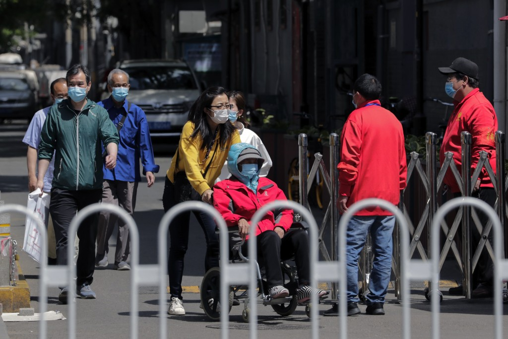 Public security volunteers wearing protective face masks to help curb the spread of the new coronavirus watch masked residents walk out from a closed ...