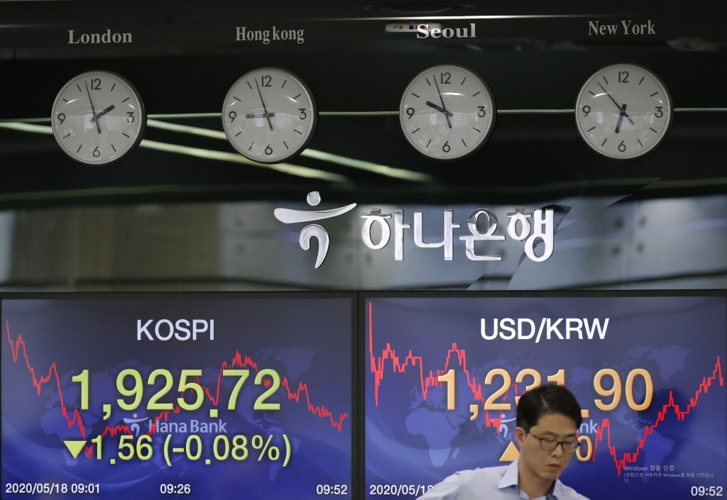A currency trader works near the screens showing the Korea Composite Stock Price Index (KOSPI), left, and the foreign exchange rate between U.S. dolla...