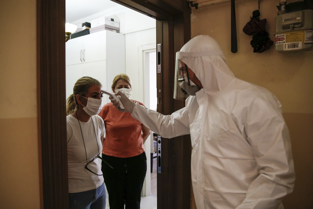 In this Friday, May 15, 2020 photo, a contact tracer with Turkey's Health Ministry's coronavirus contact tracing team, clad in white protective gear, ...
