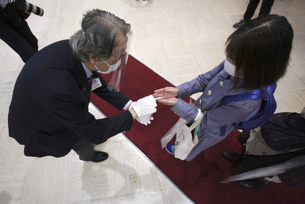 Customers are spayed with disinfectant as they arrive at the partially reopening of the Takashimaya Department Store during the coronavirus outbreak i...