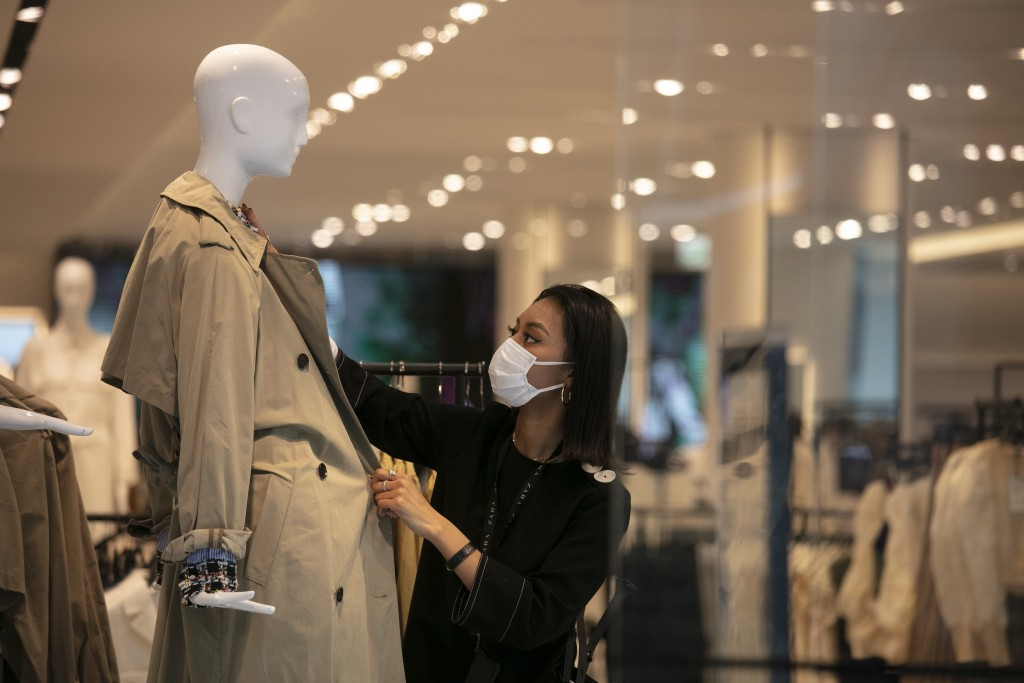 FILE - In this March 1, 2020, file photo, a department store employee with a mask dresses a mannequin in Tokyo. Japan's economic growth plunged into r...