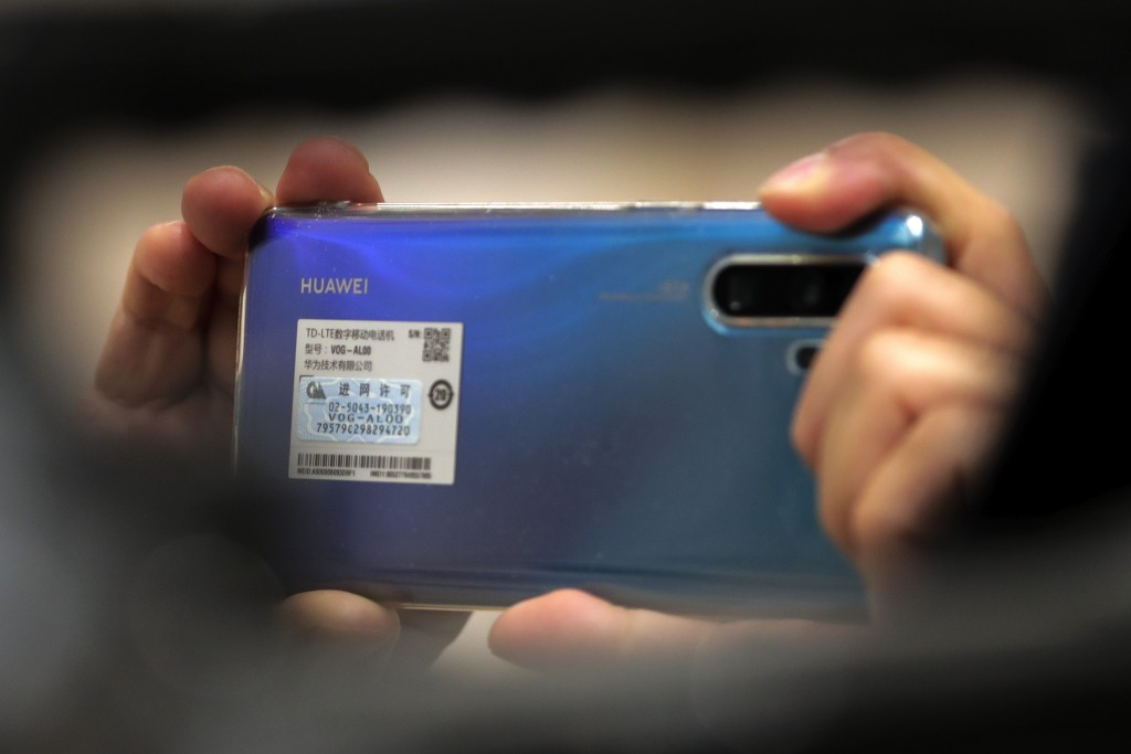 A reporter uses a Huawei smartphone to take picture during a press conference by Chinese Commerce Minister Zhong Shan at the State Council Information...