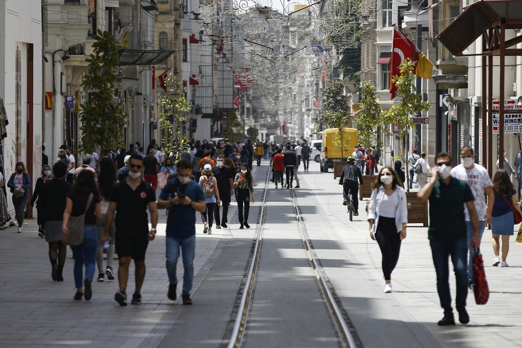 FILE - In this Friday, May 15, 2020 file photo, people walk along Istiklal street, the main shopping street in Istanbul, a few hours before the weeken...