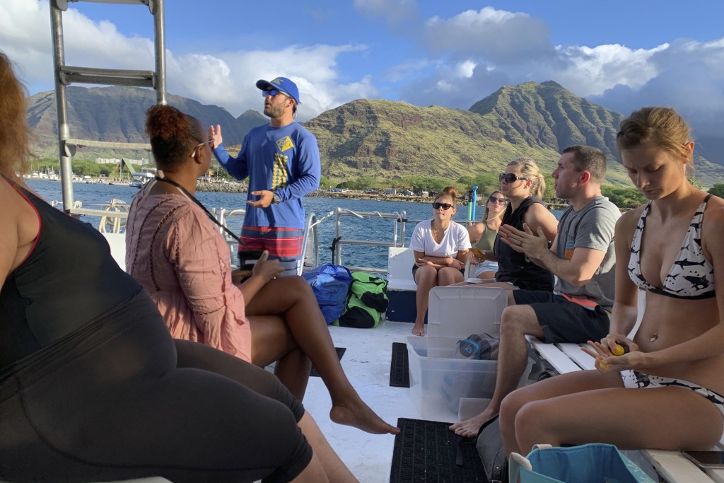 This undated photo provided by EO Waianae Tours shows Bryce Hunter talking to passengers on board a tour boat in Waianae, Hawaii. The coronavirus pand...
