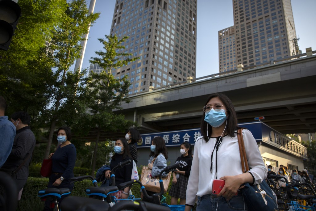 Commuters wearing face masks to protect against the new coronavirus walk through the central business district in Beijing, Tuesday, May 19, 2020. Chin...