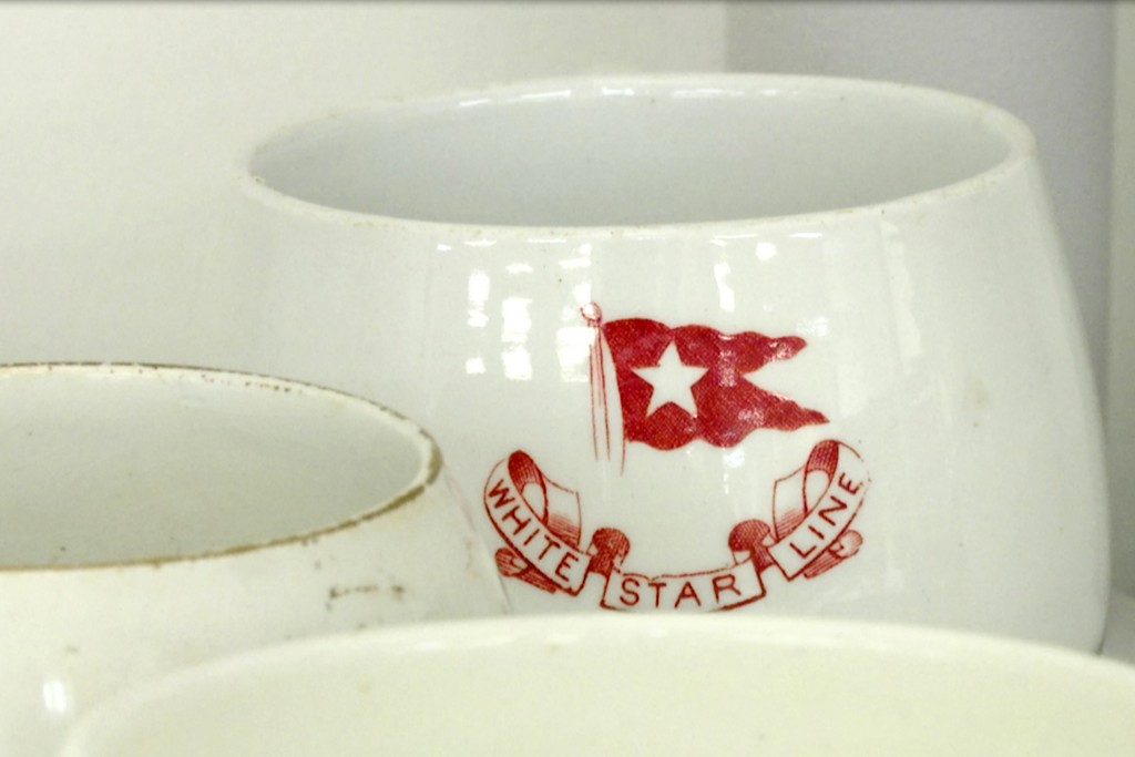FILE - In this Feb. 18, 2020 file photo, a mug displaying the logo of British shipping company White Star Line, which operated the Titanic, at RMS Tit...