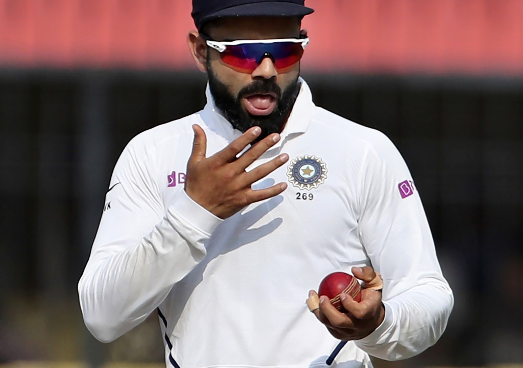 In this Nov. 16, 2019, file photo, India's captain Virat Kohli shines the ball during their cricket test match against Bangladesh in Indore, India. A ...