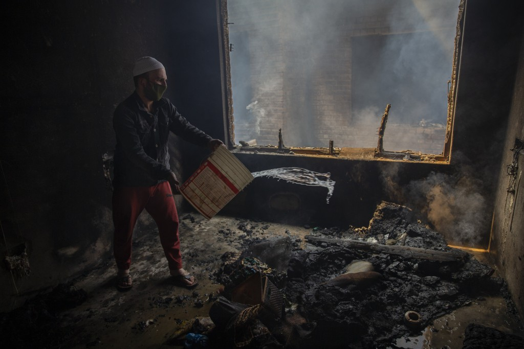 A Kashmiri man douses a fire in a house which was damaged in a gun-battle in Srinagar, Indian controlled Kashmir, Tuesday, May 19, 2020. Indian govern...