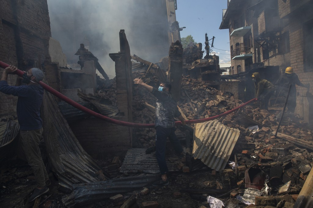 Kashmiri men and fire fighters douse a fire in a house which was destroyed in a gun battle in Srinagar, Indian controlled Kashmir, Tuesday, May 19, 20...