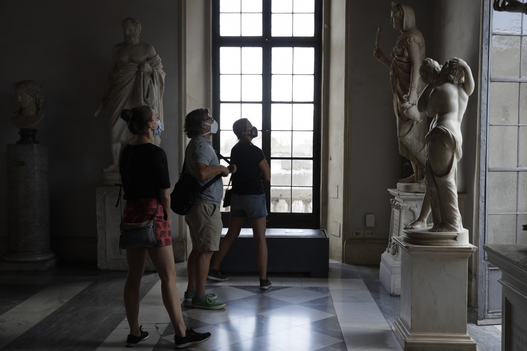 Visitors wearing a face masks to prevent the spread of COVID-19 admire statues in the Rome Capitoline Museums, including the second century A.D. Roman...