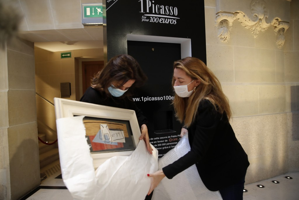 """Raffle organizers Peri Cochin, left, and Arabenne Reille unbox the painting """"Nature morte"""" by Picasso at Christie's auction house, Tuesday, May 19, 20..."""